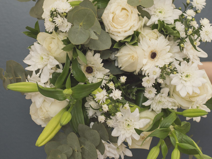 A classic white rose and St Joseph lily bouquet with penny gum and greenery